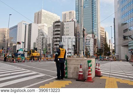 Tokyo, Japan - December 1, 2018:  Japanese Construction Workers Stand To Wait For Traffic Light Befo