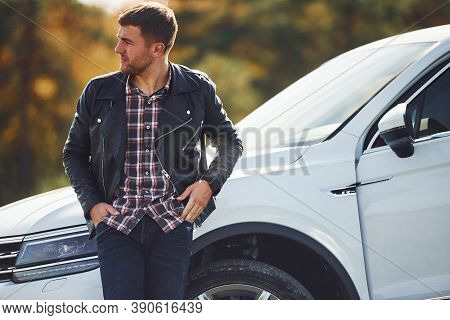 Man In Black Leather Jacket Stands Near His Parked White Car Outdoors And Waits For Help.