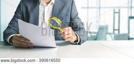 Businessman Or Tax Inspector Analyzing Document With Magnifying Glass In Office. Business Financial