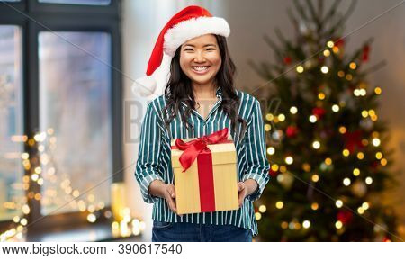 winter holidays and people concept - happy asian young woman in santa helper's hat with gift box over christmas tree on background