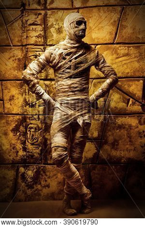 Halloween mummy is posing against the background of ruined wall. Halloween. Ancient Egyptian mythology.