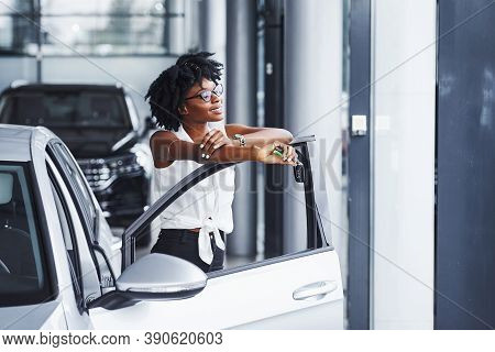 Young African American Woman In Glasses Stands In The Car Salon Near Vehicle With Keys In Hands.
