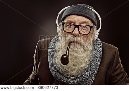 An angry old man with a gray beard, headphones and a pipe in his mouth is staring at the camera. Dark background. Old age concept.