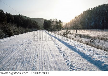 Tire Tracks In The Snow, Winter Road, Empty Road In Winter Goes Far To The Horizon, Covered With Sno