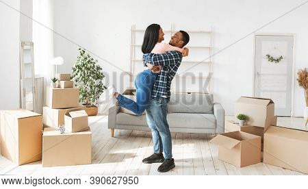 Home Relocation Concept. Happy Black Guy Hugging And Lifting His Lovely Wife In Their New Apartment,