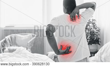 Back And Neck Pain. Black Man Suffering Backache Touching Aching Neck And Back Sitting In Bed At Hom