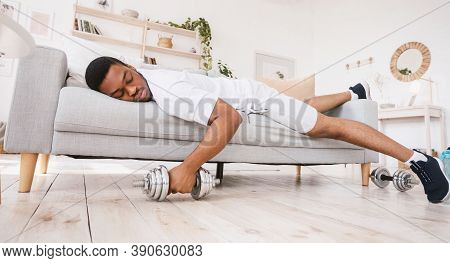 Exhausted African American Guy Sleeping Holding Dumbbell Lying On Sofa After Exhausting Workout Trai