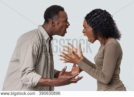 Fight During Isolation. Angry Black Man And Woman Shouting At Each Other Over Grey Studio Background