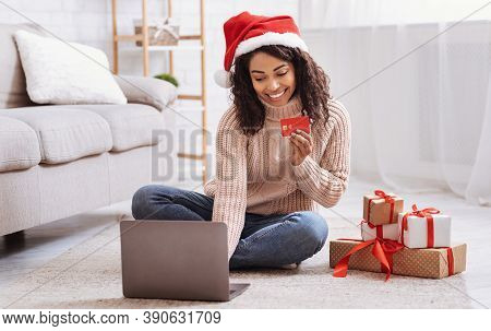 Christmas Online Shopping. Smiling Black Female Model Wearing Santa Hat Holding Red Credit Card And