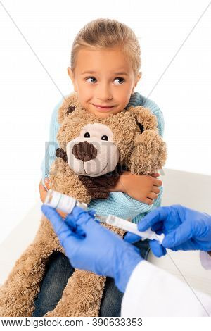 Focus Of Smiling Girl Holding Soft Toy Near Pediatrician With Vaccine And Syringe Isolated On White