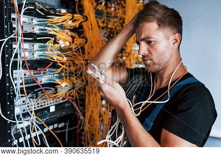 Young Man In Uniform Feels Confused And Looking For A Solution With Internet Equipment And Wires In
