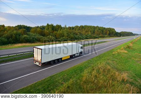 White Truck With Semi-trailer Driving Along Highway On The Sunset Background. Goods Delivery By Road
