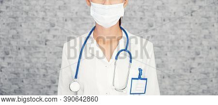 Doctor Woman Makes Stopping Hand Gesture. Girl Doctor Wearing Protection Face Mask Against Covid-19.