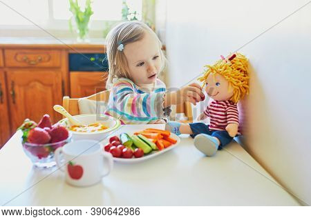 Adorable Toddler Girl Eating Fresh Fruits And Vegetables For Lunch. Child Feeding Doll And Teddy Bea