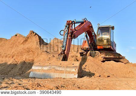 Bucket Wheel Excavator On Earthmoving. Backhoe Digs Sand On Blue Sky Background. Construction Machin