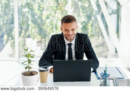 Handsome Smiling Businessman In Elegant Suit Working On Laptop In A Bright Modern Office. Business S