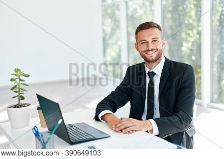 Stylish Smiling Businessman In Elegant Suit Sitting At His Desk In A Bright Modern Office. Business