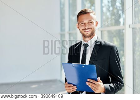 Handsome Smiling Businessman With Clipboard In A Bright Modern Office With Copy Space. Business Conc