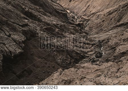 Dark Aged Shabby Landslip Surface Divided By Huge Cracks And Layers. Coarse Brown Mud And Clay Or Ro