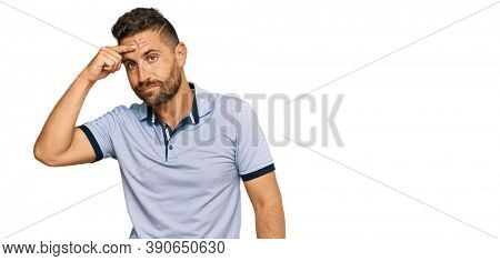 Handsome man with beard wearing casual clothes pointing unhappy to pimple on forehead, ugly infection of blackhead. acne and skin problem