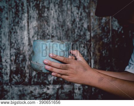 Child Or Poor Homeless Holding Plastic Bowl With Hungry And Asking Help Food Donation From Traveler
