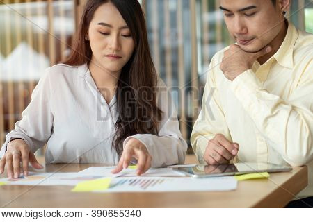 Unhappy Asian Couples Are Calculating Income And Expenses To Cut Unnecessary Expenses. Concepts For