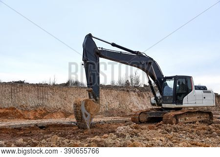 Excavator Working On Earthmoving At Open Pit Mining. Backhoe Digs Sand And Gravel In Quarry. Heavy C