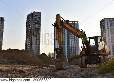 Excavator On Earthmoving At Construction Site. Backhoe Dig Pit Foundation. Construction Machinery An