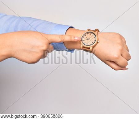 Hand of caucasian young businesswoman wearing wristwatch. Pointing with finger to watch over isolated white background