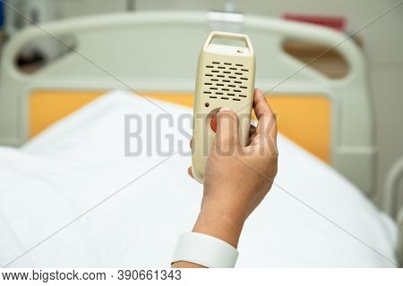 Woman Holding And Pushing Hand Emergency Button In Hospital Patient Room; Hand Press To Call Nurse F