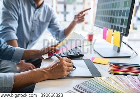 Two Colleagues Creative Graphic Designer Working On Color Selection And Drawing On Graphics Tablet A