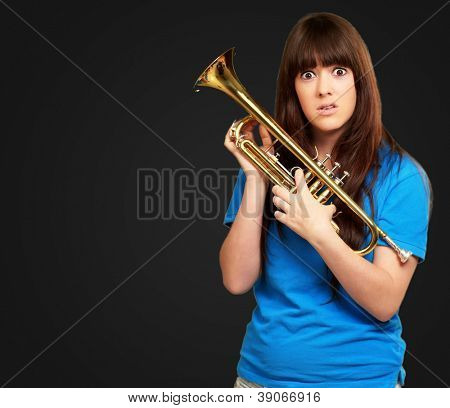 portrait of a teenager holding trumpet on black background