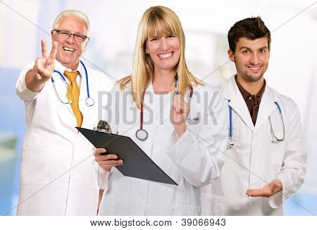 Happy Female Doctor Holding Clipboard In front Of Happy Male Doctors, Indoors