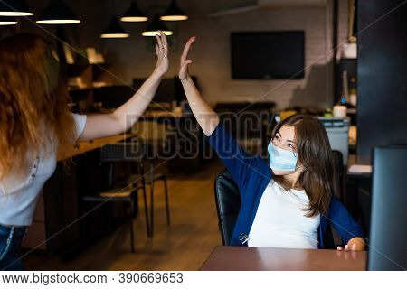 Co-workers In Protective Masks Give A High Five In The Office. Women Work During The Coronavirus