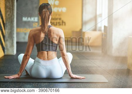 Power Of Meditation. Rear View Of Woman In Sportswear Sitting On Yoga Mat In Lotus Pose At Gym And P