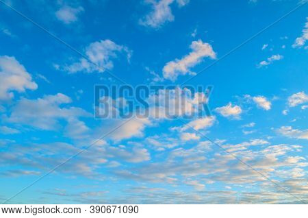 Blue sky background, white dramatic fluffy clouds lit by sunset light. Vast sky landscape scene, sky background, sunset sky nature. Sky landscape, cloudy sky view, panoramic sky background