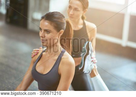Exercising With Fitness Instructor. Young Beautiful Caucasian Woman Doing Stretching Exercises With