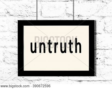 Black Wooden Frame With Inscription Untruth Hanging On White Brick Wall