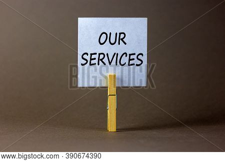 White Paper With Text 'our Services', Clip On Wood Clothespin. Beautiful Grey Background. Business C