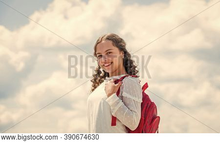 Happy Curly Girl Hold Backpack On Sky Background. Back To School. Childhood Happiness. Small Kid In