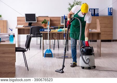 Young male contractor cleaning the office