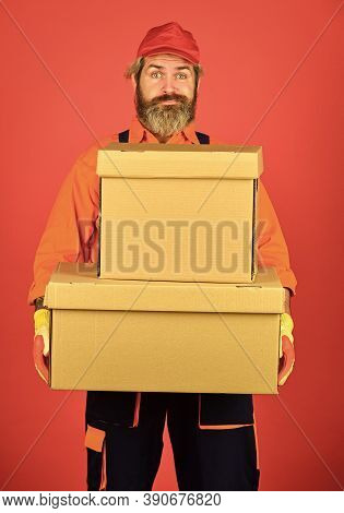 Man Builder In Boilersuit Hold Boxes. Moving To New Apartment. Happy Man Cardboard Box. Carrying Box