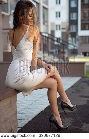 A Gorgeous Smiling Brunette Woman In A Light Dress Is Sitting On An Outdoor Bench. Enjoying The Sun