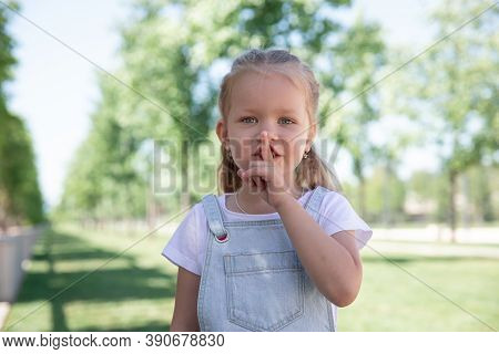 Closeup Portrait Of Little Girl Holding Her Finger To Her Lips.