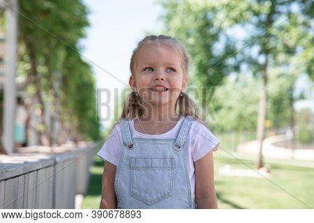A Little Girl Smiles, Shows Her Teeth. Large Portrait.