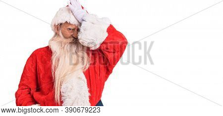 Old senior man with grey hair and long beard wearing traditional santa claus costume surprised with hand on head for mistake, remember error. forgot, bad memory concept.
