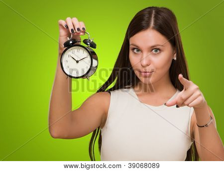 Woman Holding Alarm Clock and pointing against a green background