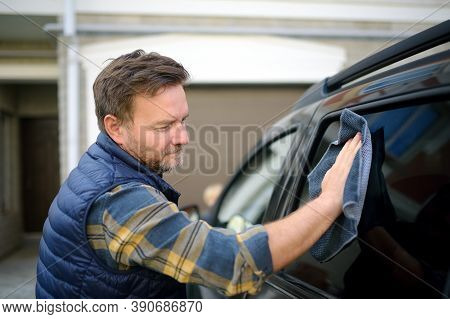 A Mature Man Cleans His Car With Rag. Driver Washes The Glass Of His Car Using Microfiber Washcloth.