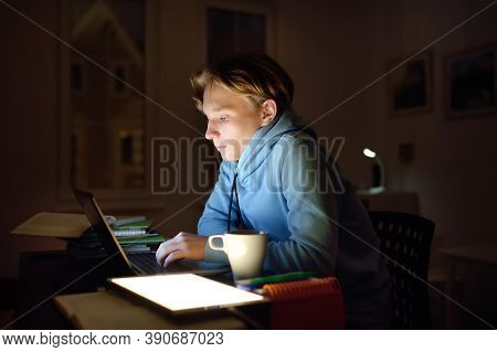 Concentrated Young Man Working Late Night At Home Office With Laptop And Tablet. Remote Working, Dis