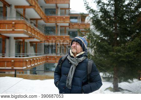 Mature Man Walking On Street Of Mountain Resort Town In Switzerland, Europe. Winter Vacation. Ski Re